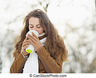 Young woman drinking hot beverage in winter park