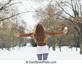 Young woman with hot beverage in winter park. Rear view