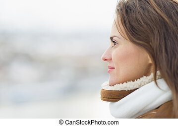 Young woman looking into distance in winter outdoors