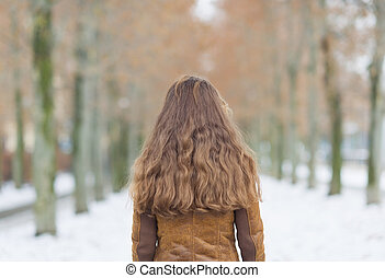 Young woman in winter park. rear view