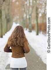 Young woman walking in winter park. rear view