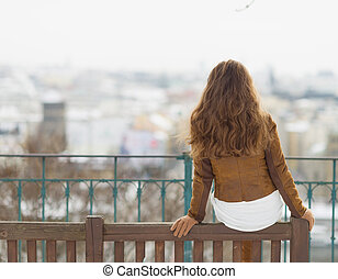 Young woman sitting on bench in winter outdoors. rear view