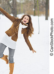 Happy young woman having fun in winter park