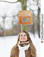 Happy young woman looking on bird feeder on tree in winter park