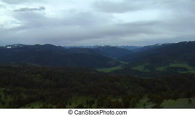 Aerial shot of forested mountains, grey clouds in background