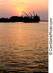 Cargo ship in the harbor at sunset