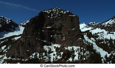 Aerial shot of snowy mountain faces on blue-sky day