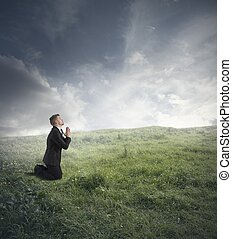 Businessman praying - Businessman is praying to solve the...
