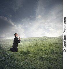 Businessman praying - Businessman is praying to solve the...