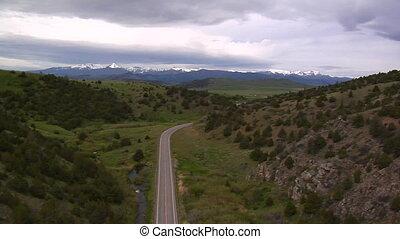Aerial shot of highway cutting through mountains, grey skies