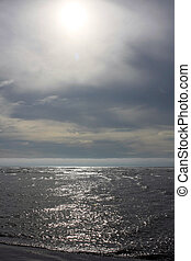 Sun over the ocean - A scene of the sun reflectiong over the...