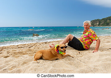 man laying with dog at the beach - Relaxing elderly man with...