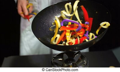 Chef tossing mixed vegetables in a
