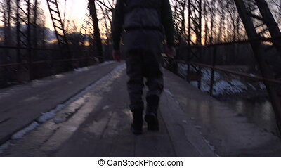 camera follows fly fisherman walking across bridge in winter