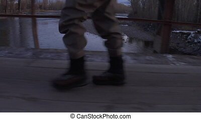 fly fishermen in boots walks across bridge with river in distance