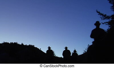 silhouettes of cowboys in predawn light