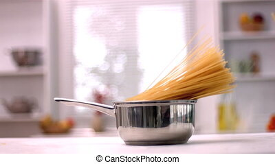 Spaghetti falling in saucepan in kitchen in slow motion