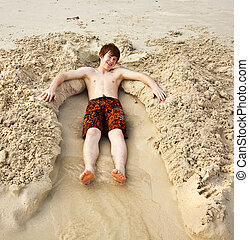 boy is lying in a sandy bed at the beauti ful beach - boy...