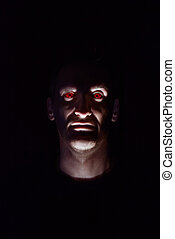 Halloween - Head of the man with red eyes on a black...