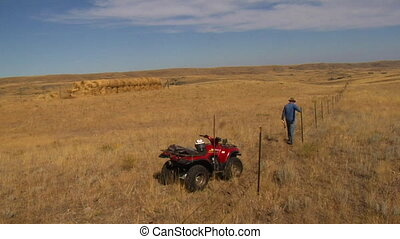 cowboy inspects fencing