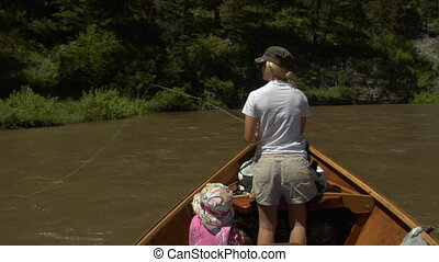 Woman flyfishing from driftboat on river