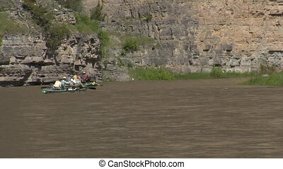 Several river rafts float rocky canyon