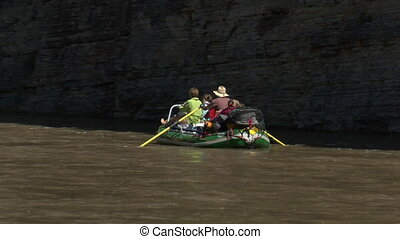 Family on river raft in rocky canyon