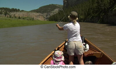 Woman flyfishing from driftboat on river 3