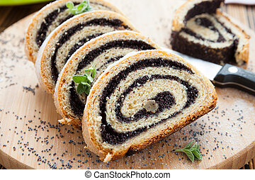 poppy seed Roll on a wooden surface, closeup