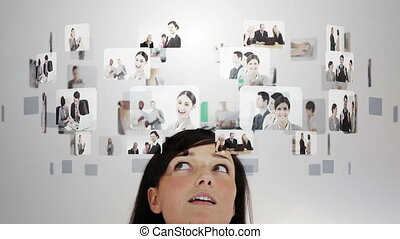 Woman pondering various business situations displayed in...