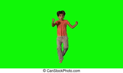 Boy jumping and cheering on green screen in slow motion
