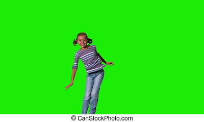 Smiling girl jumping up and down on green screen in slow...