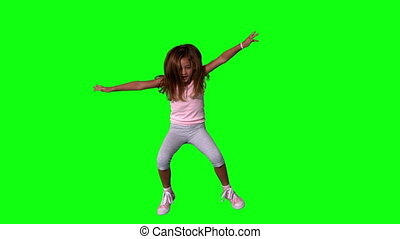 Cute little girl jumping with limbs outstretched on green...