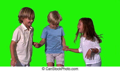 Siblings holding hands and jumping on green screen in slow...