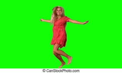Attractive blonde jumping on green