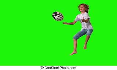 Boy jumping up to catch rugby ball on green screen in slow...