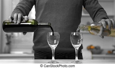 Man pouring red and white wine into two glasses in slow...