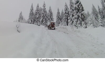 Bulldozer moving on snowy road, slow motion
