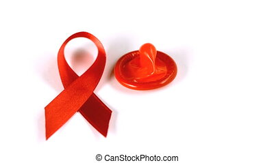 Condom falling over beside red ribbon in slow motion