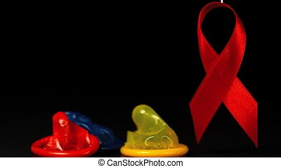 Coloured condoms dropping down beside red ribbon in slow...