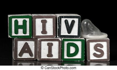 Condom falling on blocks spelling Aids and Hiv in slow...