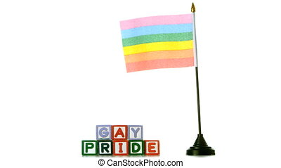 Rainbow flag blowing in the wind beside gay pride blocks on...