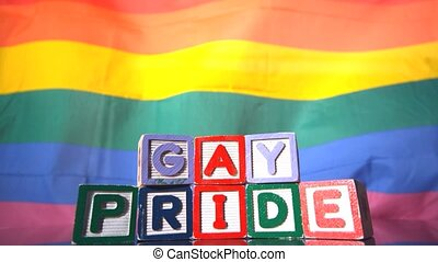 Rainbow flag moving in the breeze with gay pride blocks in...