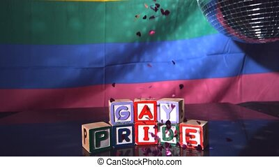 Heart confetti falling on blocks spelling gay pride in slow...