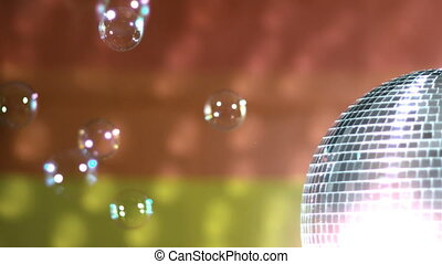 Shiny disco ball spinning with floating bubbles against...