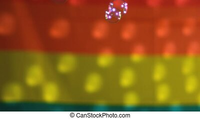 Bubbles floating against rainbow flag in slow motion