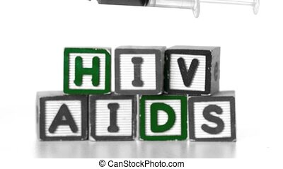 Needle falling in front of blocks spelling AIDS and HIV in...