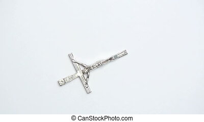 Silver crucifix on white background