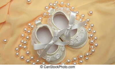 White baby booties with string of pearls on revolving yellow...