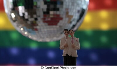 Gay groom cake toppers in front of rainbow flag with...